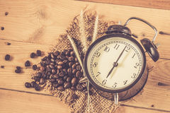 Arabica coffee bean with vintage clock. On wood background, wake up morning time with coffee concept Stock Photos