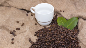 Arabica coffee beans in a burlap bag. Grain coffee mugs on a background of the bag. Green leaves of coffee Royalty Free Stock Images