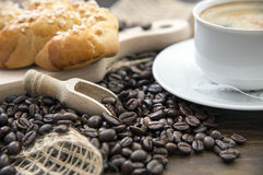 Arabica  coffee beans with a cup of coffee. Coffee beans with a cup of black coffee and pastry, on a brown wood board Stock Photography