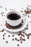 Arabica coffee beans and cup full of coffee. Black roasted arabica coffee beans and cup full of coffee Stock Photography