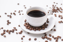 Arabica coffee beans and cup full of coffee. Black roasted arabica coffee beans and cup full of coffee Stock Photos