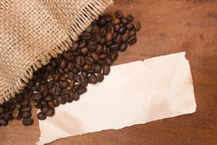 Arabica coffee beans. Poured out of a bag on a wooden surface Royalty Free Stock Images