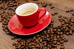 Arabica coffee beans and red espresso mug. On a wooden table Royalty Free Stock Photography
