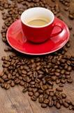 Arabica coffee beans and red mut on a black brown wooden table. Arabica Kaffebohnen und rote Espressotasse auf einem dunklem Tisch aus Holz Royalty Free Stock Photo