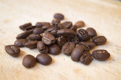 Arabica coffee beans on wooden surface. Close up, the main ingredient of energizing morning espresso based beverage Stock Image