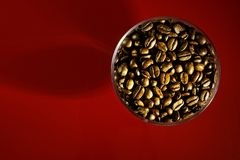 Arabica roasted coffee beans in a glass bowl. Red background royalty free stock photo