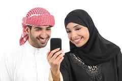 Arabisch paar die sociale media op de slimme telefoon delen stock afbeeldingen