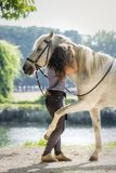 Arabisch paard die zijn eigenaar Irene Gefaell koesteren die natuurlijke dressuur in het park in Pontevedra, Spanje, in augustus  stock fotografie