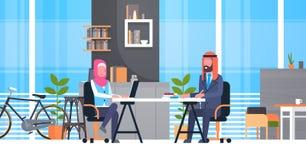 Arabische Bedrijfsman en Vrouwenzitting bij Bureau die in Moderne Coworking-Ruimte Moslimarbeiders binnen samenwerken Royalty-vrije Stock Foto