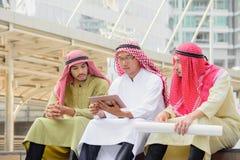 Arabische Bedrijfsmensen die en overleg zitten hebben door tablet te gebruiken Royalty-vrije Stock Foto's
