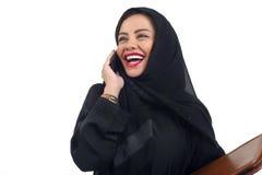Arabische bedrijfsvrouw die een omslag houdt en op de telefoon spreekt die op wit wordt geïsoleerd Stock Fotografie