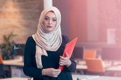 Arabische bedrijfsvrouw die een omslag in modern startbureau houden Stock Fotografie