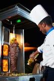 Arabische chef-kok die kebab maakt Stock Afbeeldingen