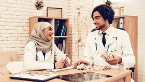 Arabische Doktoren Counting Money nach der Arbeit, Zahltag lizenzfreie stockbilder