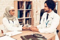 Arabische Doktoren Counting Money nach der Arbeit, Zahltag Moslemische Doktoren Counting Dollars im Büro Arabische Doktoren Holdi lizenzfreies stockbild