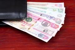 Arabische Emirate-Dirham in der schwarzen Geldbörse lizenzfreie stockfotografie