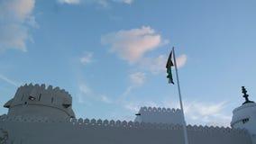 Arabische Emirate fahnenschwenkend nahe bei historisch entworfenem arabischem Gebäude stock video footage
