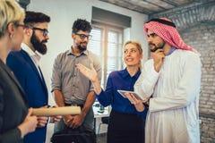 Arabische en westelijke bedrijfsmensen die over investeringen spreken royalty-vrije stock afbeelding