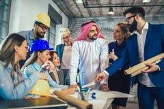Arabische en westelijke bedrijfsmensen die over investeringen spreken royalty-vrije stock foto