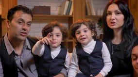 Arabische Familie, die auf Sofa sitzt und smilingly den Finger auf Kamera im Wohnzimmer zeigt stock footage