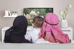 Arabische familie het letten op televisie thuis stock afbeelding
