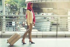 Arabische Frau, die einen Koffer tragend geht Lizenzfreie Stockbilder