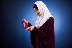 Arabische Frau im hijab bewundert Halskette im Kasten stockfotos