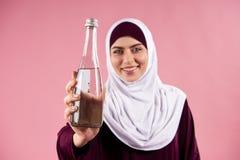 Arabische Frau im hijab hält Flasche Wasser stockfotos