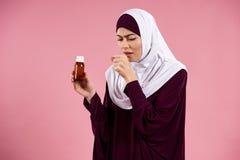 Arabische Frau im hijab mit Hustensirup lizenzfreie stockfotos