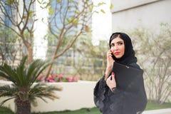 Arabische Geschäftsfrau, die an einem Handy spricht Stockbilder