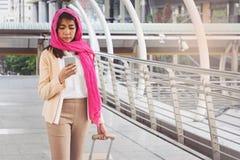 Arabische Geschäftsfraumitteilung an einem Handy in der Stadt Lizenzfreie Stockfotografie