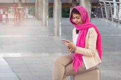 Arabische Geschäftsfraumitteilung an einem Handy in der Stadt Lizenzfreie Stockbilder