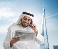 Arabische Geschäftsmannlesenachrichten mit burj khalifa lizenzfreies stockbild