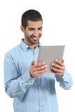 Arabische glückliche zufällige Mannholding und -lesung ein Tablettenleser stockfotos