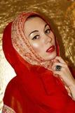 Arabische jonge vrouw Gouden samenstelling Rode etnische klerensjaal hijab, toebehoren Stock Afbeelding