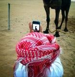 Arabische jongen die pic van kameel nemen Stock Afbeelding