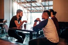 Arabische junge Männer, die im Dachbodencafé hängen Nahöstliche Leute, die im Lounge Bar sprechen und Getränke haben lizenzfreies stockbild