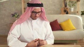 Arabische mensenzitting bij de lijst die een rozentuin in zijn handen houden en een gebed lezen stock footage