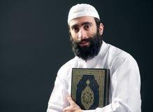 Arabische moslimmens die met baard het heilige boek Quran houdt Royalty-vrije Stock Foto's