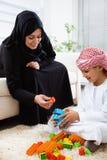 Arabische Mutter und Sohn zusammen zu Hause spielend mit Spielwaren Stockfotografie