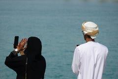 Arabische Paare, welche die Ansicht des Hafens in einer Großstadt genießen stockfoto