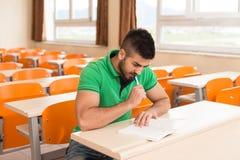 Arabische Student With Books Sitting in Klaslokaal Stock Fotografie