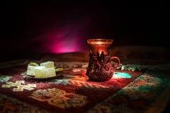 Arabische thee in glas met oostelijke snacks op een tapijt op donkere achtergrond met lichten en rook Oostelijk theeconcept Lege  royalty-vrije stock fotografie