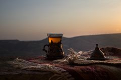 Arabische thee in glas op een oostelijk tapijt Oostelijk theeconcept Armudu traditionele kop De achtergrond van de zonsondergang  royalty-vrije stock fotografie