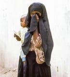 Arabische unbekannte Mutter trägt ihr Baby Stockfotografie