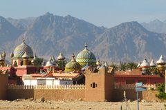 Arabische ungewöhnliche Stadt des roten Steins auf dem Hintergrund von schönen Bergen in der Wüste lizenzfreie stockfotos