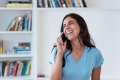 Arabische vrouw die bij mobil telefoon lachen stock foto's