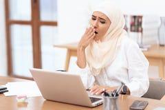 Arabische vrouw die die een headscarfzitting dragen op het werk wordt vermoeid stock foto