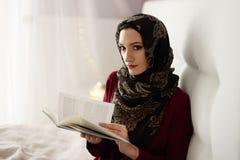 Arabische vrouw die in hijab een boek lezen stock foto