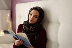 Arabische vrouw die in hijab een boek lezen stock afbeelding